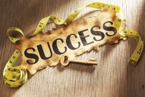 Measuring success concept using burnt paper with word success printed on it and golden key surrounded by measuring tape